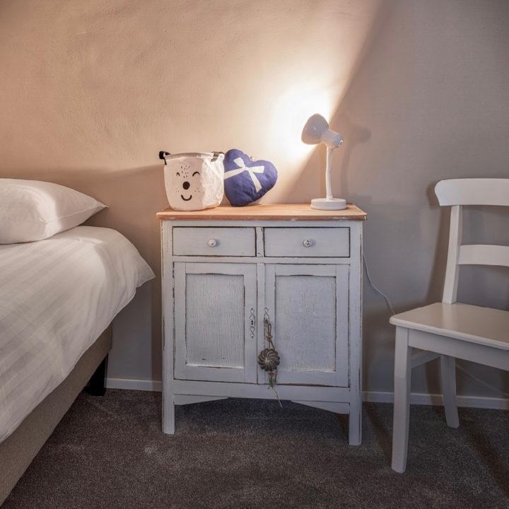 Slaapkamer met kastje, stoel, bedlampje en knuffel
