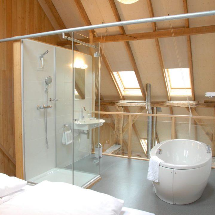Badkamer onder schuin dak, met open douche en vrijstaand bad
