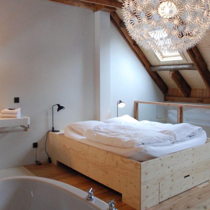 Tweepersoons bed met wit beddengoed, onder schuin boerderij dak