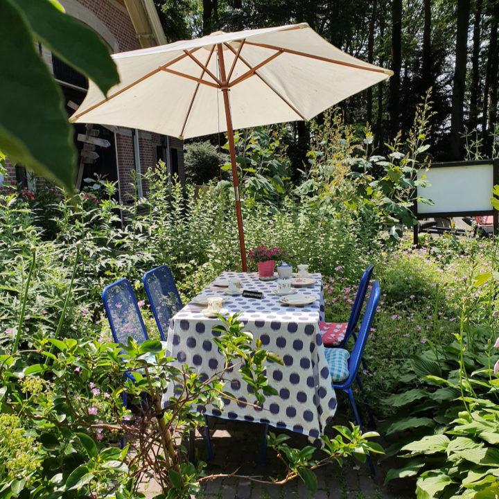 Blauwe stoelen, een gedekte tafel en een parasol in een theetuin in Enschede