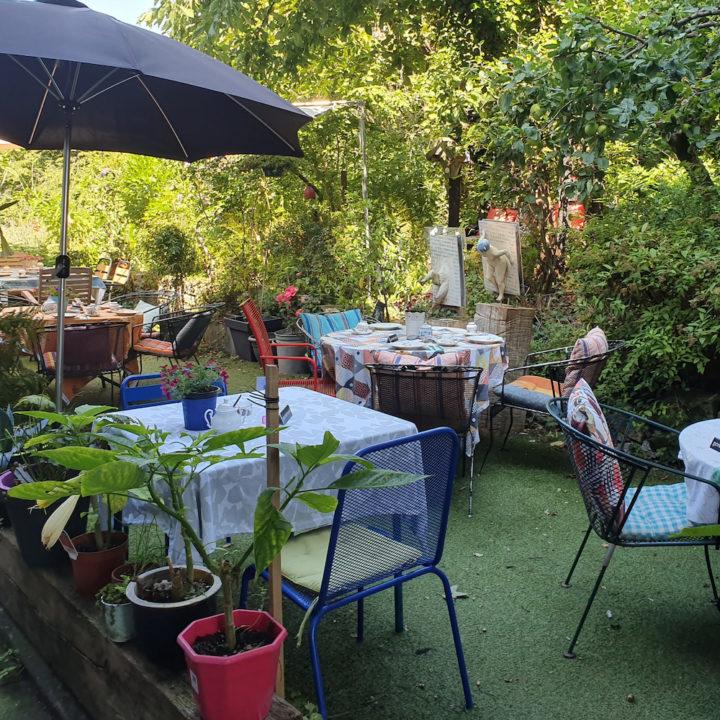 Gedekte tafeltjes in de tuin bij een theehuis