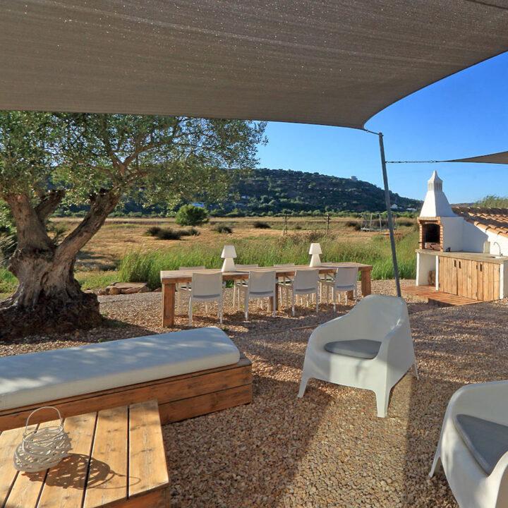 Overdekt terras met loungebank en kuipstoelen