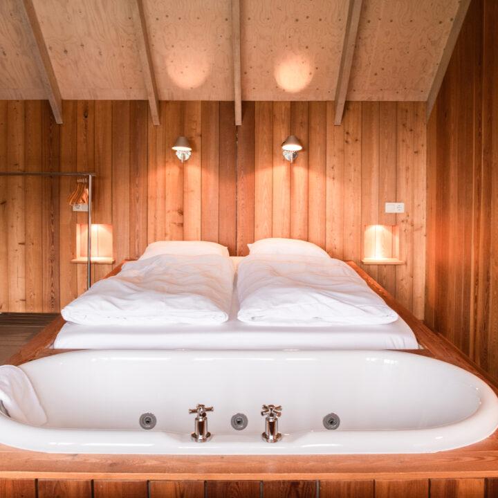 Tweepersoons bed met een bad aan het voeteneinde