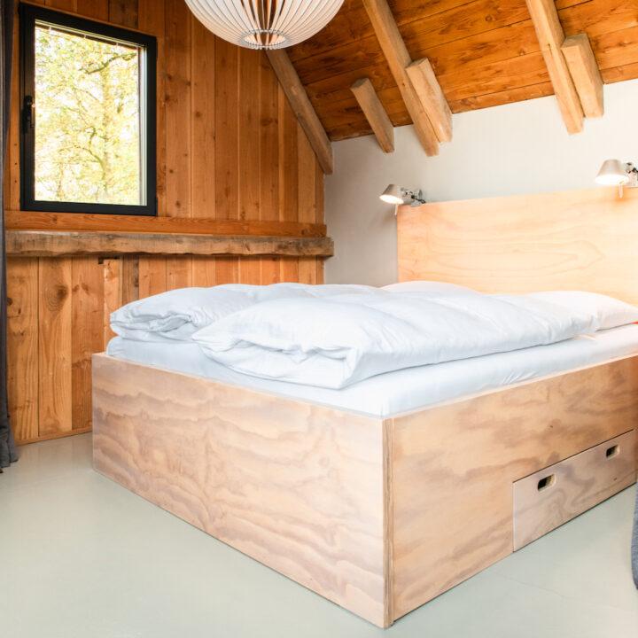 Tweepersoons bed met een houten ombouw
