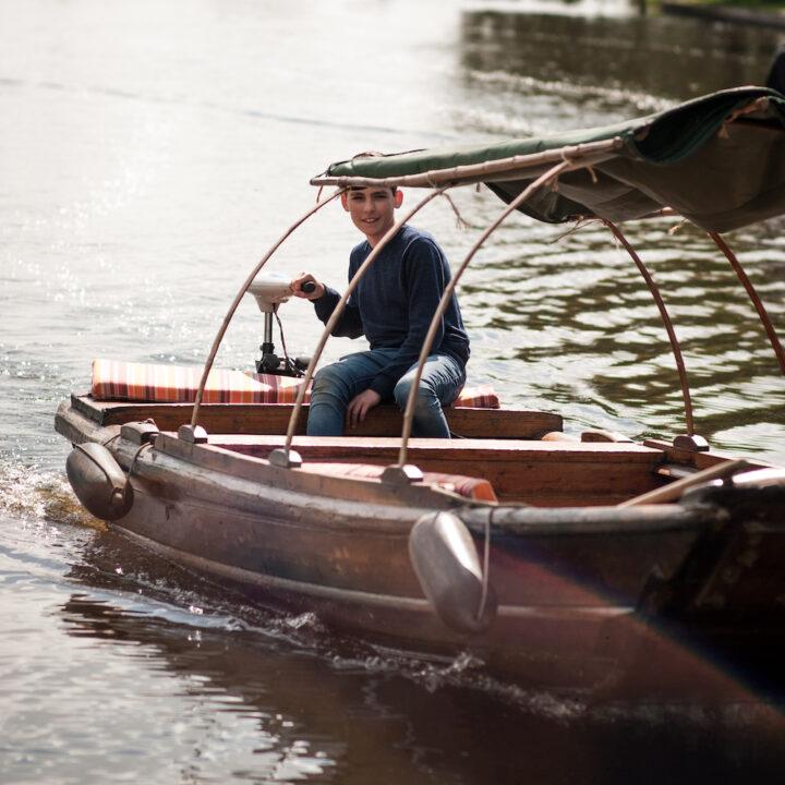 Jongen aan het stuur van de fluisterboot