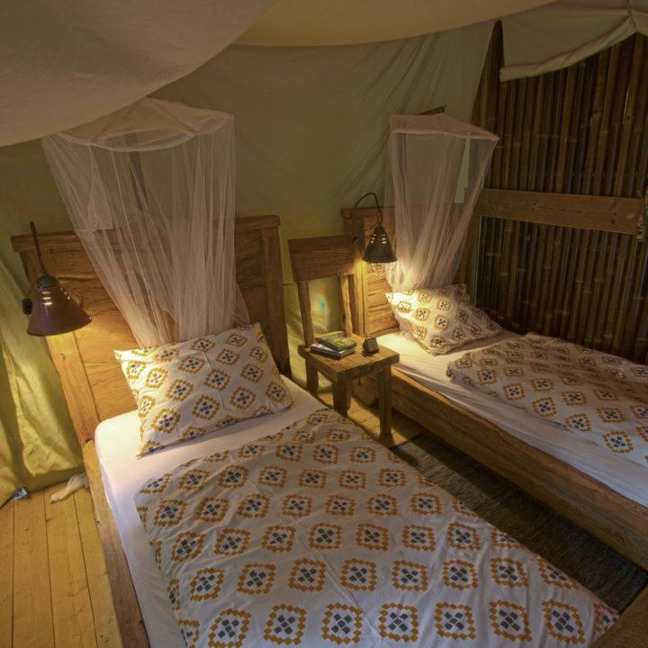 Twee opgemaakte bedden met een muggennet erboven