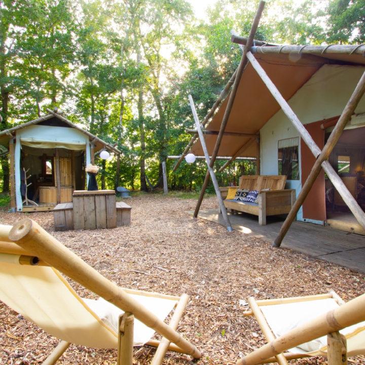 Safaritent met douche huisje en ligstoelen voor de tent