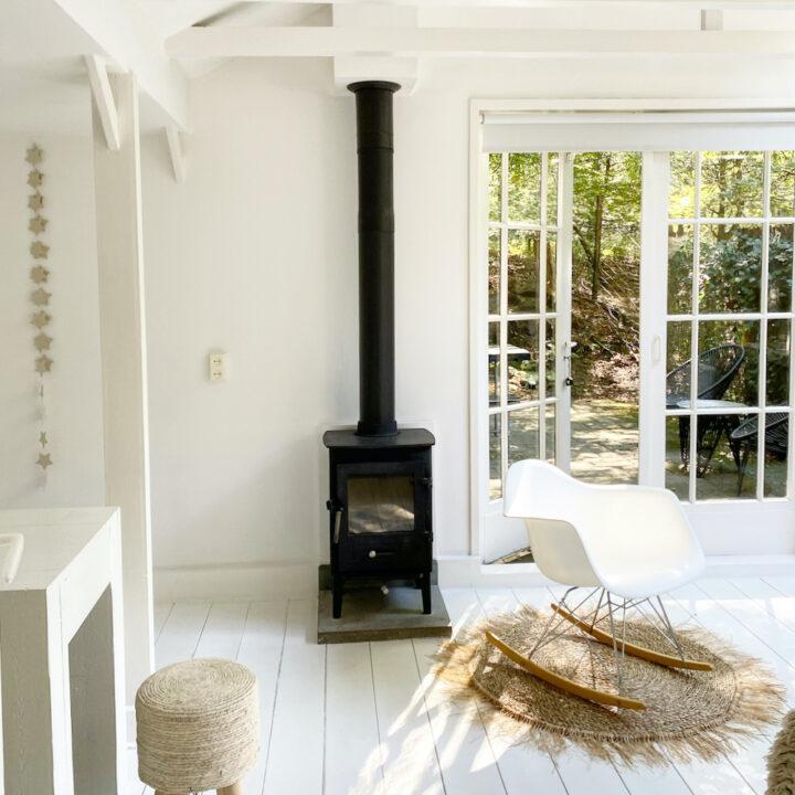 Wit huisje met witte schommelstoel en zwarte houtkachel