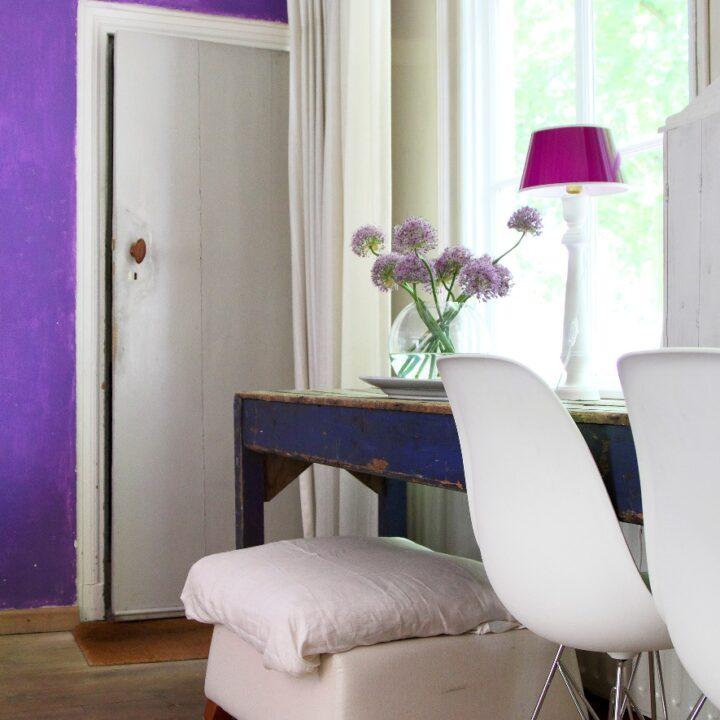 Blauwe houten tafel met vaas bloemen en witte stoelen in de B&B kamer