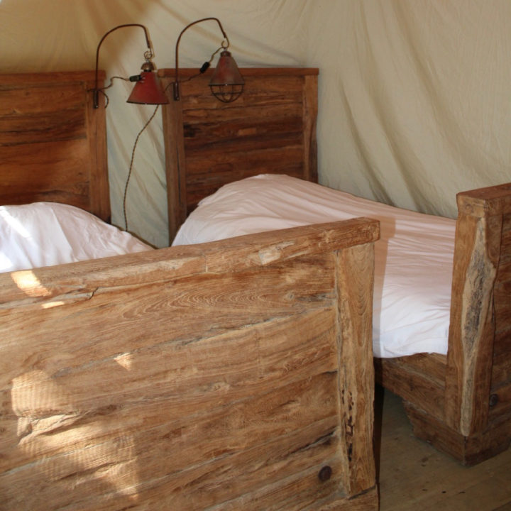Twee losse houten bedden in een safaritent