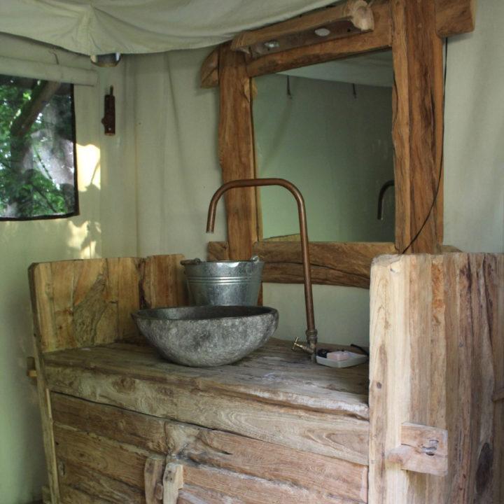Stenen wastafel met koperen kraan op houten kastje