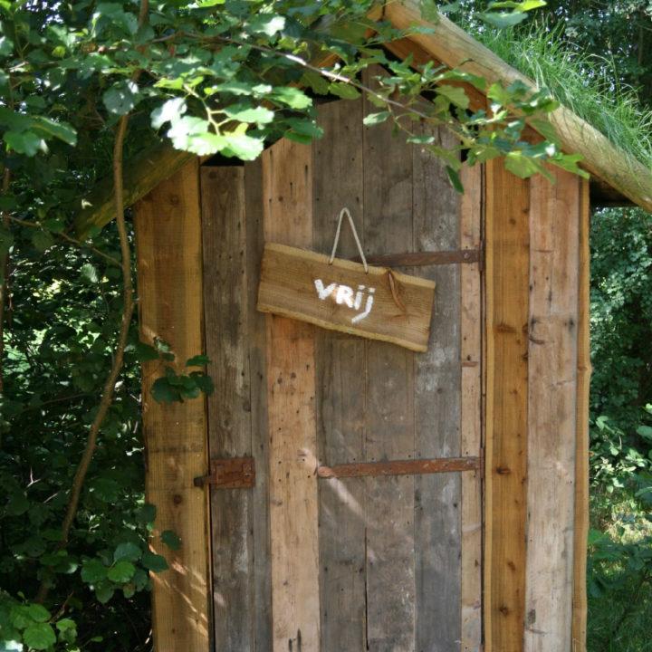 WC hokje van hout tussen de bomen met bordje VRIJ