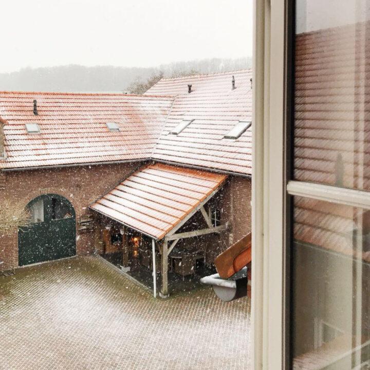 Doorkijkje vanuit het raam op witte daken