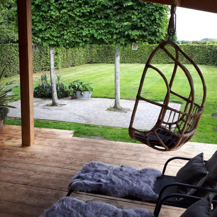 Een hangstoel onder de veranda met zicht op een grote open tuin met twee bomen er in