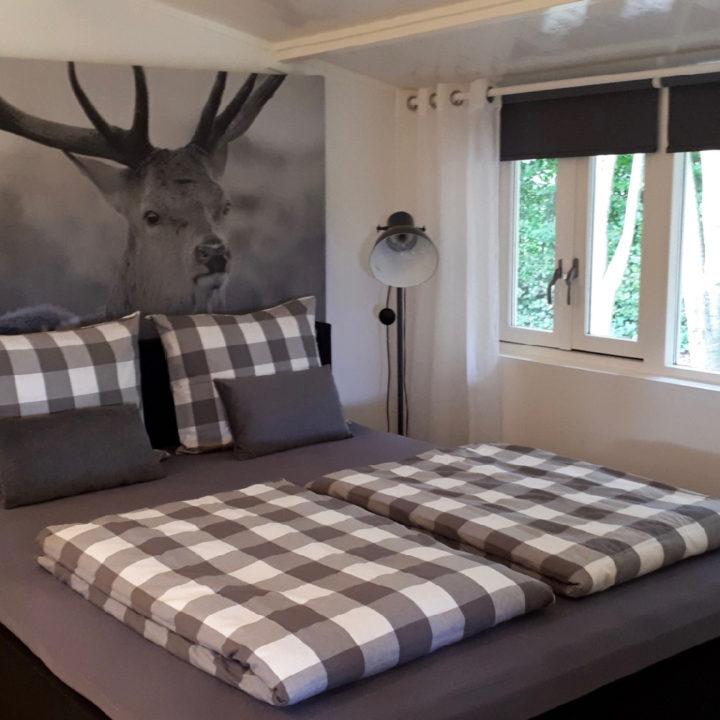Een opgemaakt bed met open ramen en een grote foto van een hert aan de muur