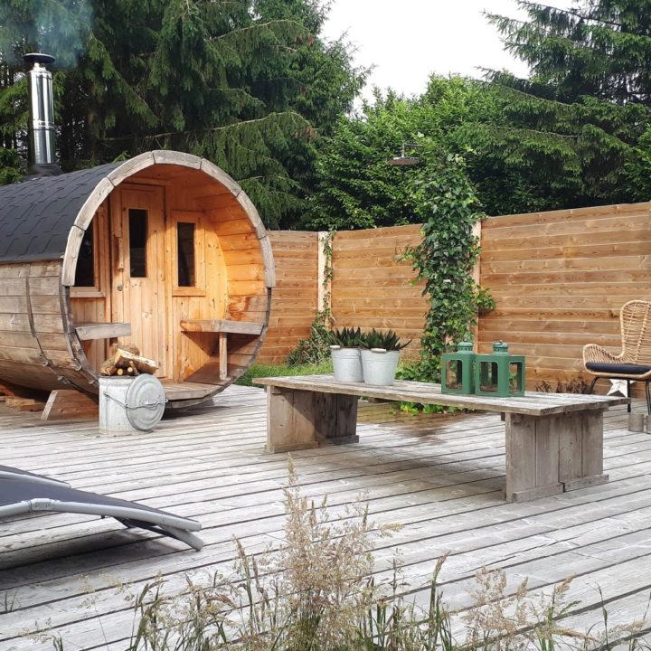 Een terras met een houten cabine voor de sauna