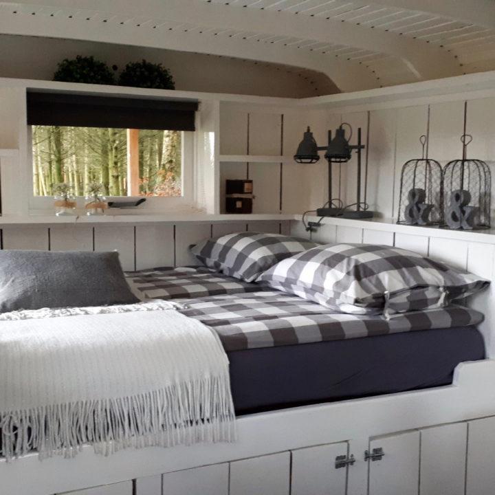 Een opgemaakt tweepersoonsbed met decoraties op het nachtkastje