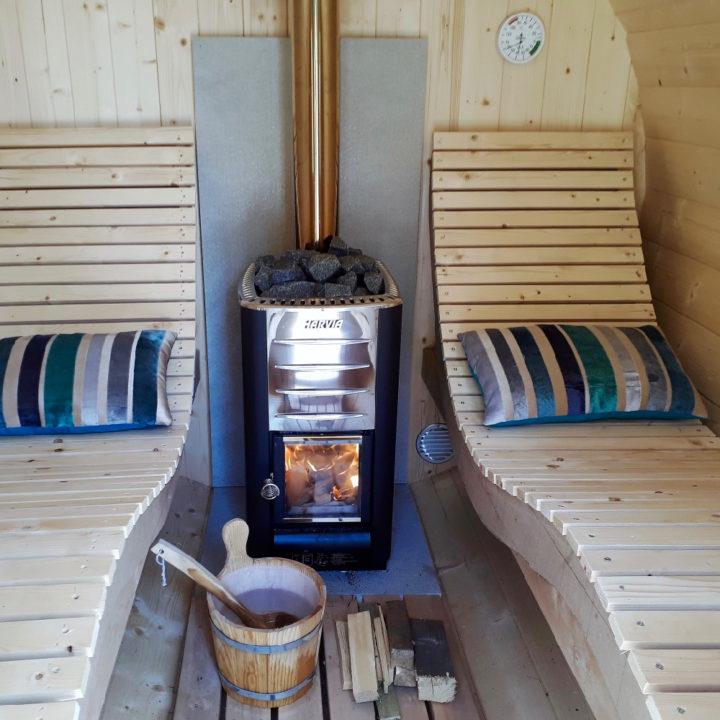Een houtkacheltje in een sauna met twee houten banken er naast