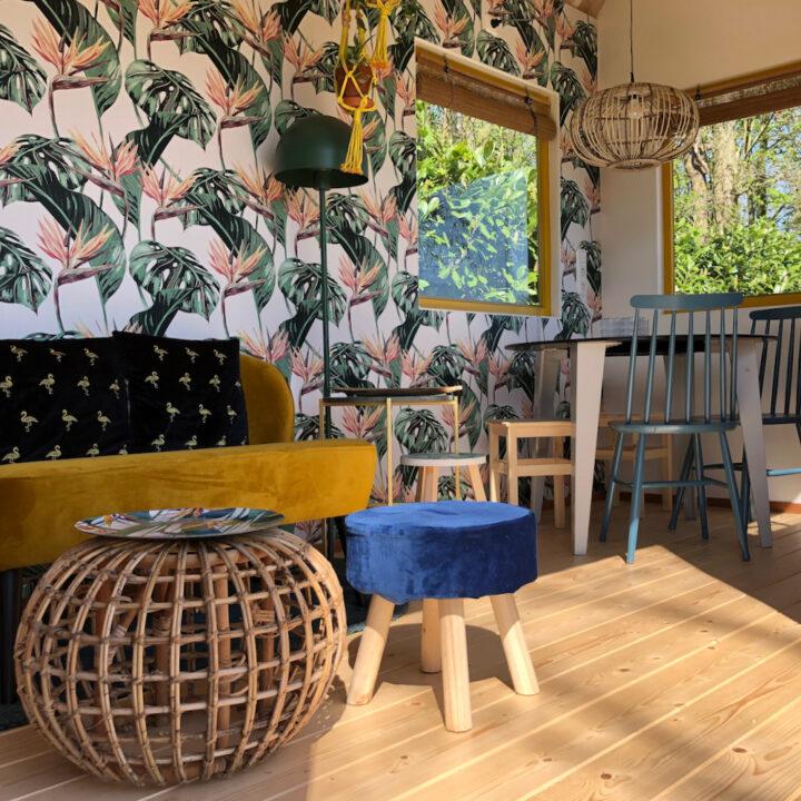 Huisje met geel fluwelen bankje, palmbladeren behang en eethoek