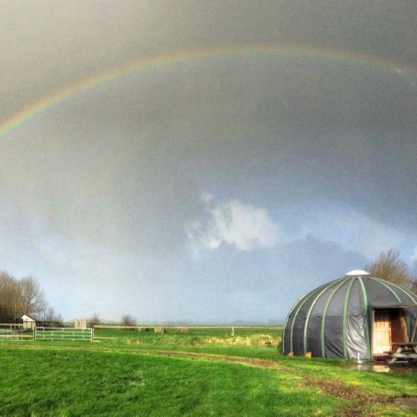 Iglo in het gras met regenboog op de achtergrond