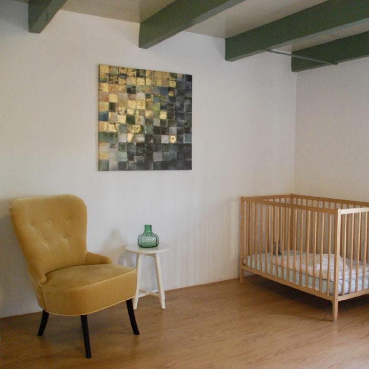 Kinderbedje en geel fauteuiltje in een slaapkamer