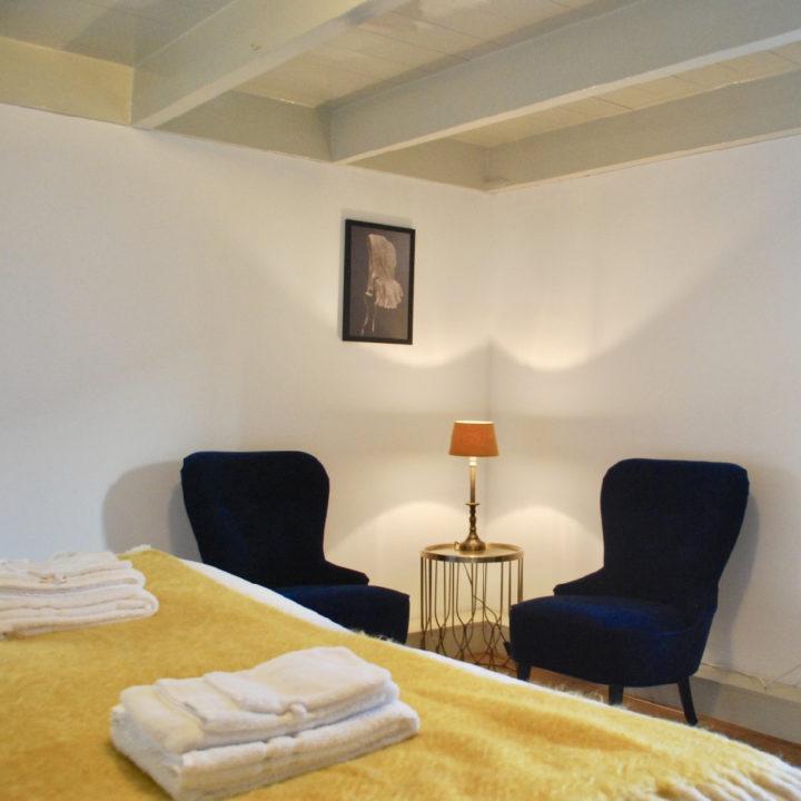 Slaapkamer met tweepersoons bed met gele sprei en blauwe fauteuils