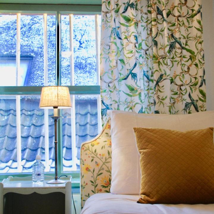 Een van de slaapkamers van Boerderij de Rit, een opgemaakt bed met mooie kussens en lief bloemetjesbehang