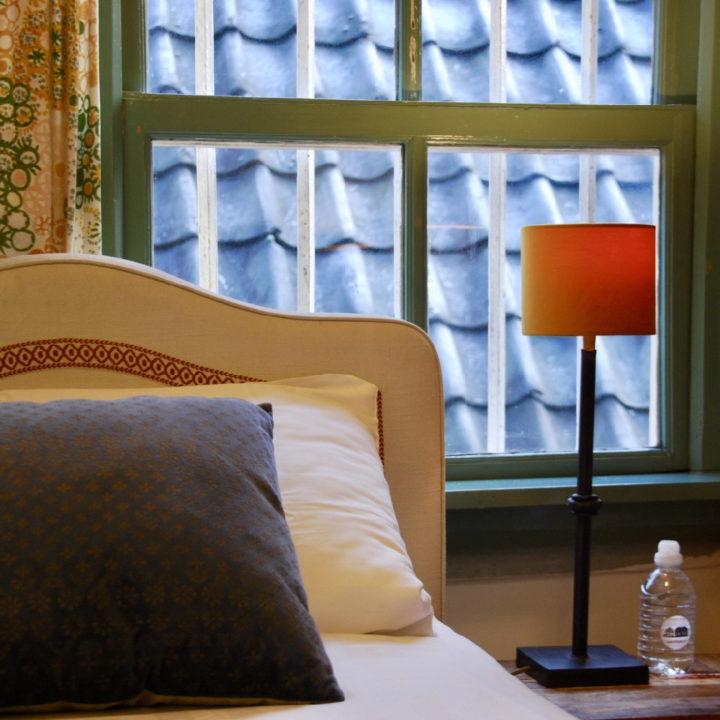 Hoofdeinde van een bed voor het raam, rode schemerlamp ernaast