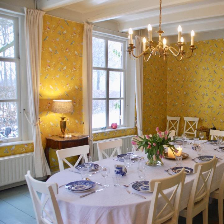 Ovale gedekte eettafel in eetkamer met geel behang