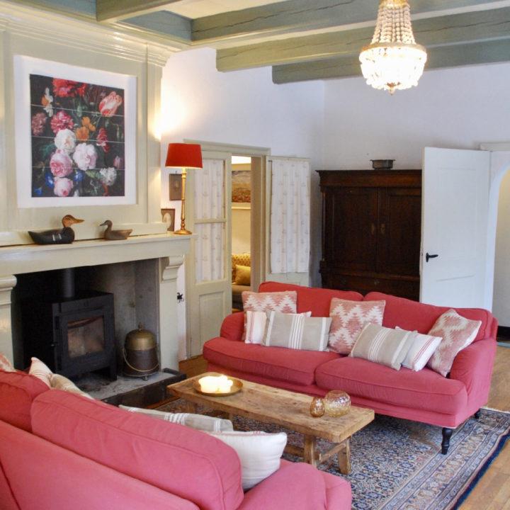 Zithoek met rode banken, een salontafel en een schouw met open haard
