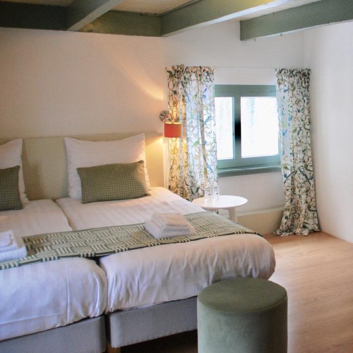 Een opgemaakt tweepersoons bed met wit en zacht groen met klein boerderijraam