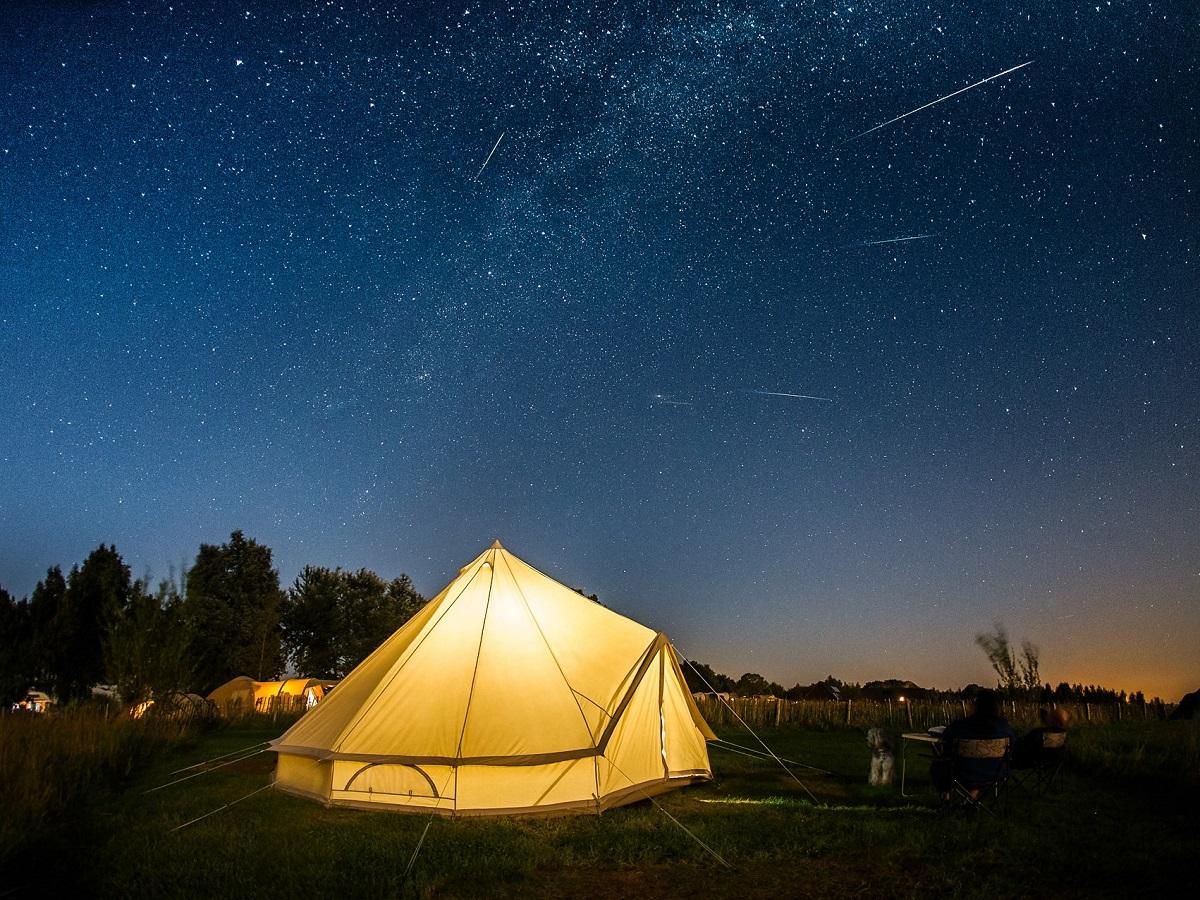Verlichte belltent onder een sterrenhemel, op een kleine camping