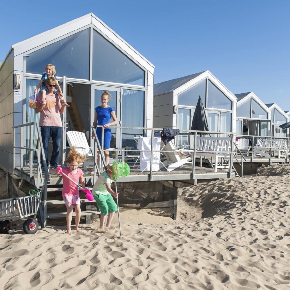 Strandhuisjes met een gezin spelend in het zand