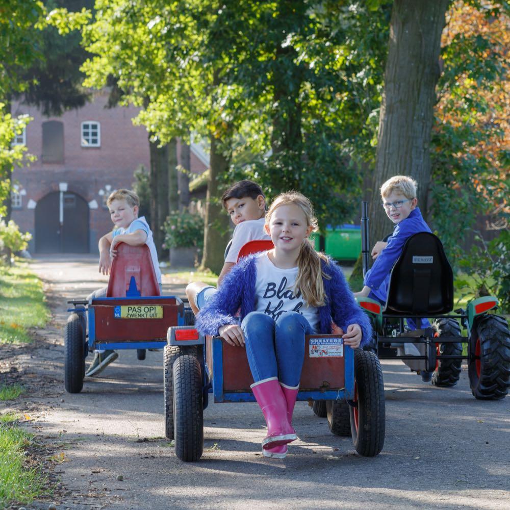 Gezinsvakantie op de boerderij, kinderen op skelters
