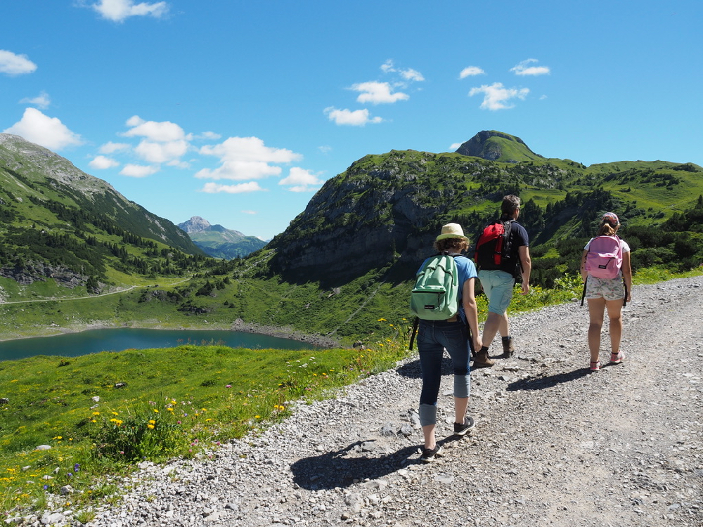 Vader met twee dochters aan het wandelen langs een bergmeer