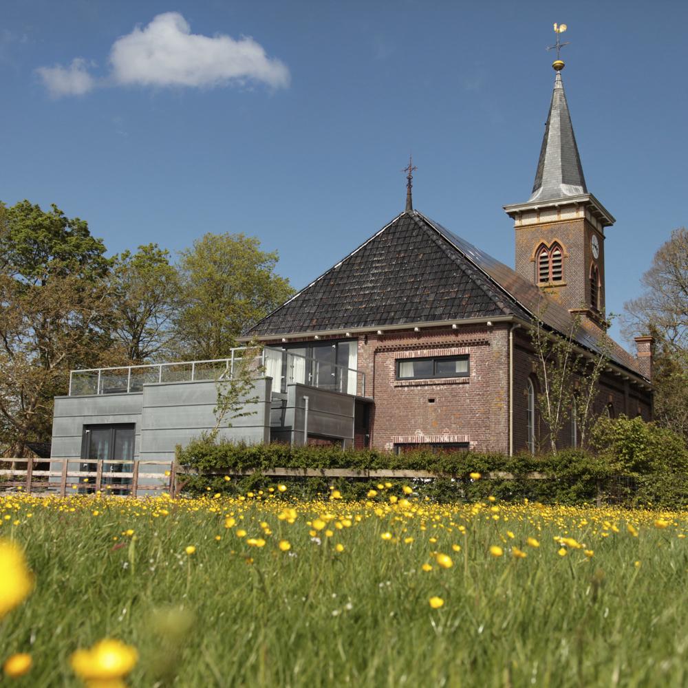 Een vakantiehuisje in de weide met een kerk op de achtergrond