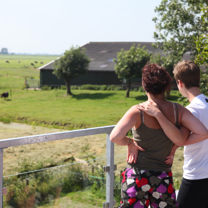 Een man en een vrouw kijken naar een boerderij