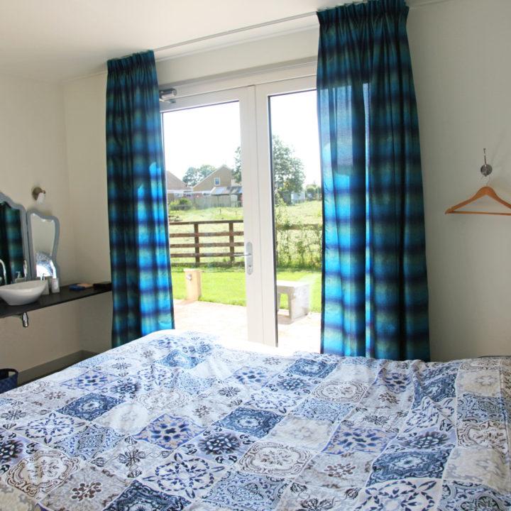 Bed met blauwe dekens met een deur dat uitzicht toont op de weides