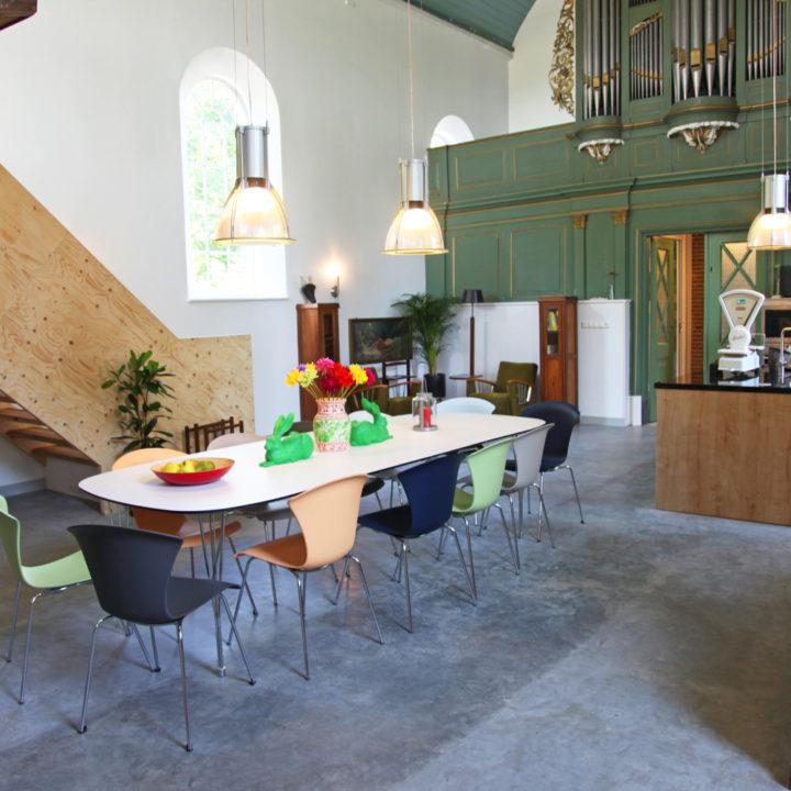 Een lange tafel met kleurrijke stoelen in de eethoek