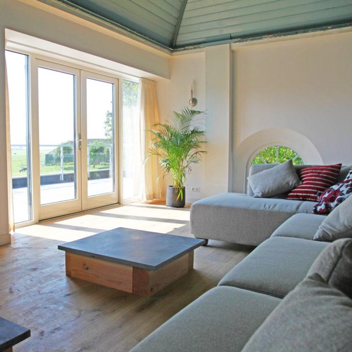 Comfortabele bank in de woonkamer, met een uitzicht op weides