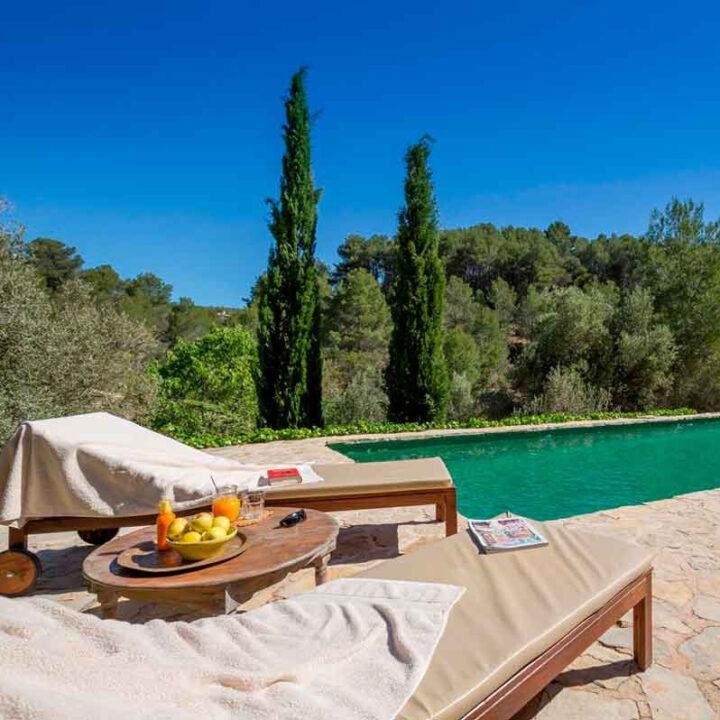 Ligbedden met fruit en sapjes aan de rand van het zwembad