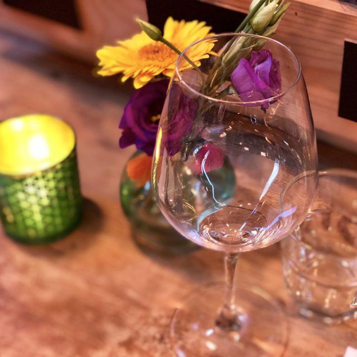 Glas wijn en bloemetjes en branden kaars