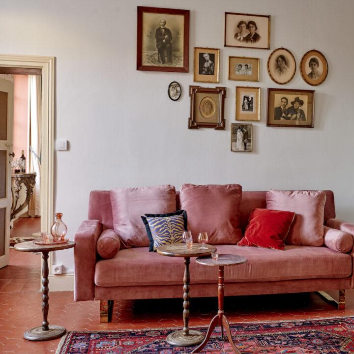 Roze fluwelen bank met schilderijtjes erboven