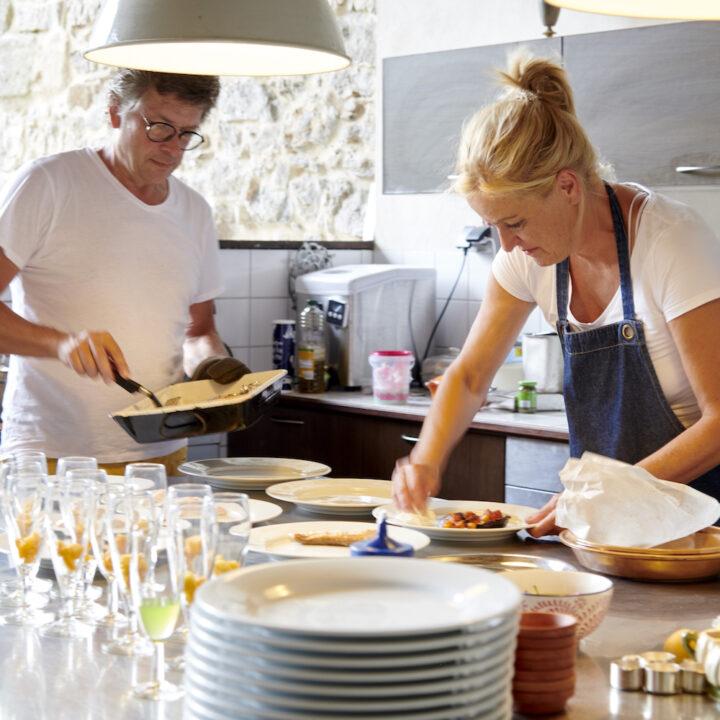 Gastheer en gastvrouw koken voor de gasten