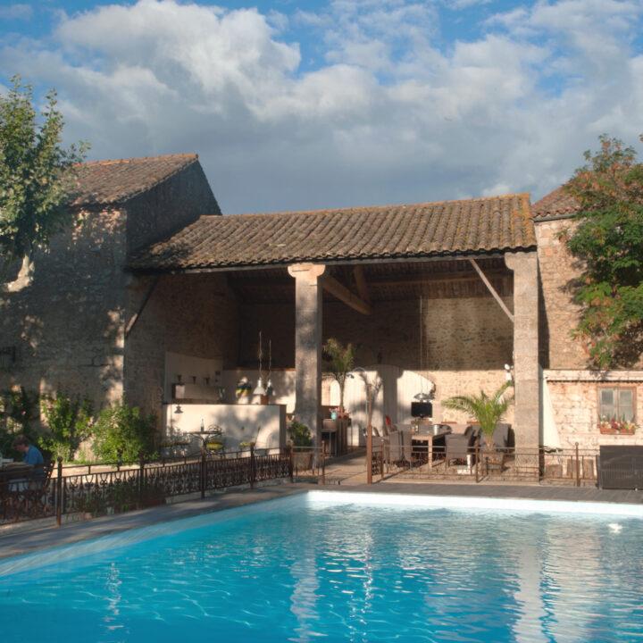 De geweldige patio, met zwembad en lange tafels.
