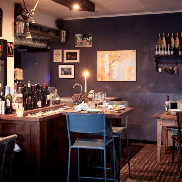 Het restaurant van Gasterie Lieve Hemel, met een houten tafel met blauwe stoelen, wijnflessen, een brandende kaars