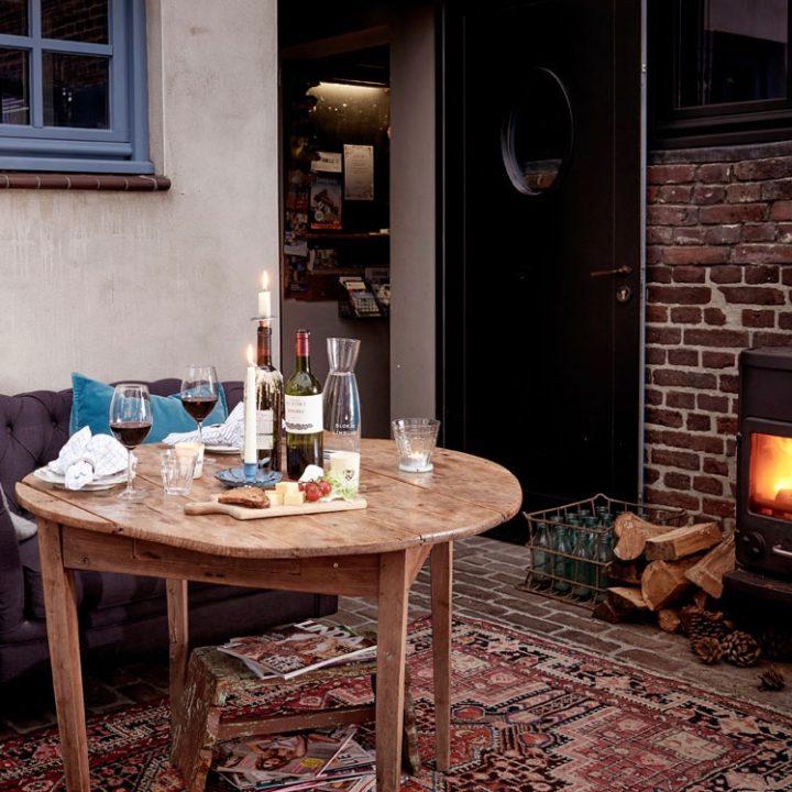 Serre met bank, ronde tafel met wijnglazen en borrelplank, brandende haard
