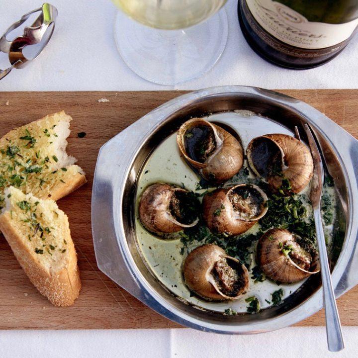 Slakken als voorgerecht met glas witte wijn en stokbrood