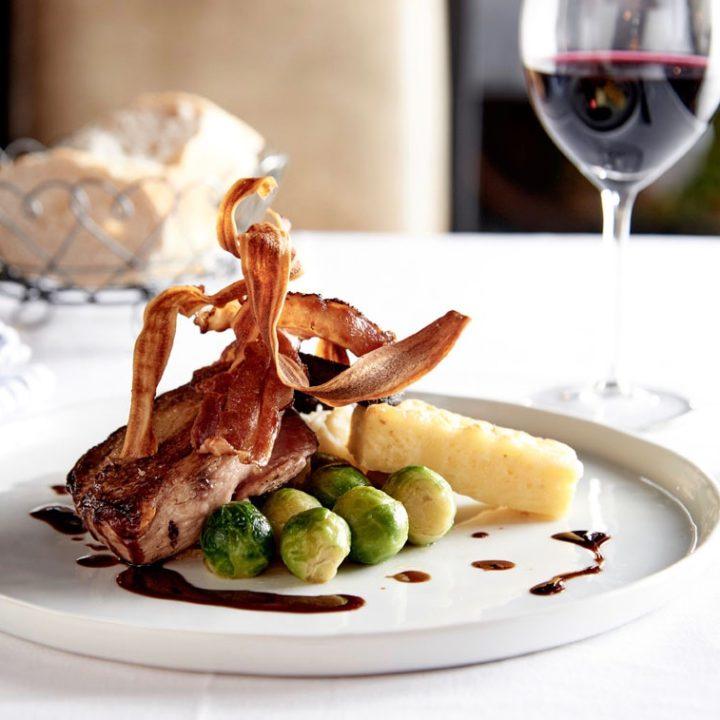 Bord met spruitjes, aardappels en vlees, glas rode wijn ernaast