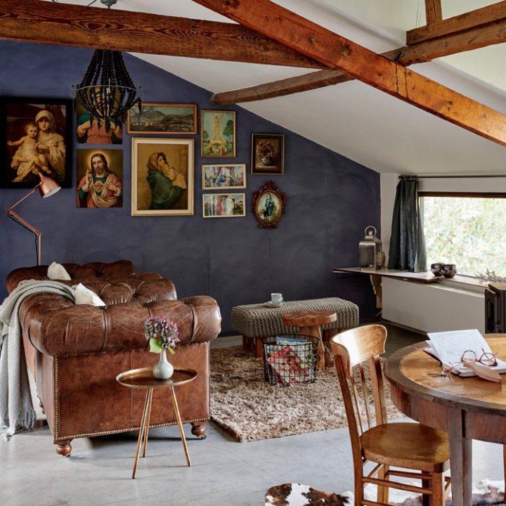 Woonkamer onder schuin dak met bruine Chesterfield bank, blauwe wand en schilderijen